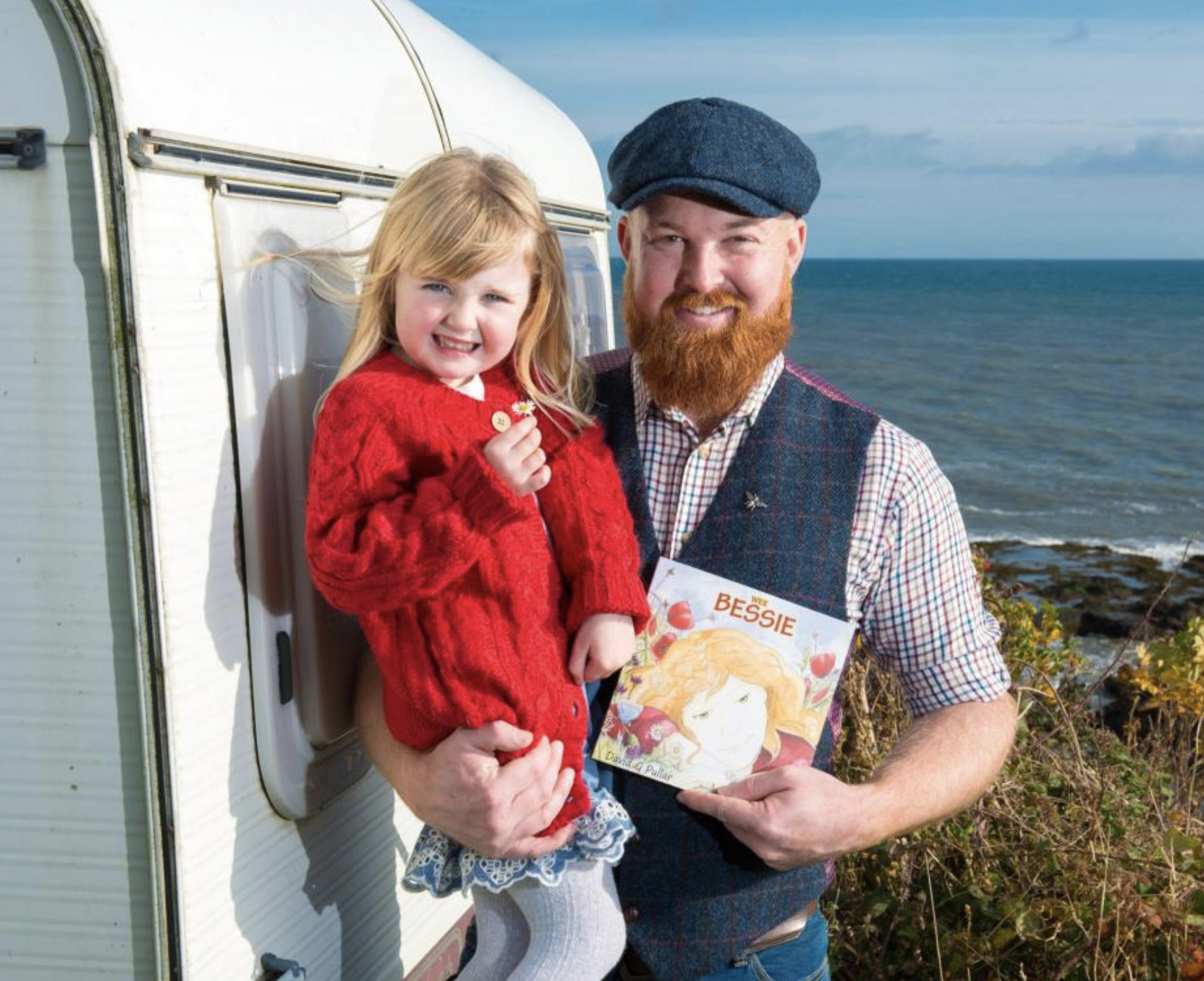 David Pullar holding his daughter and his children book Wee Bessie. A white trailer to the left and the ocean to the right.