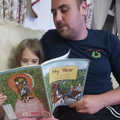 Young girl reading book with her dad sat on the sofa