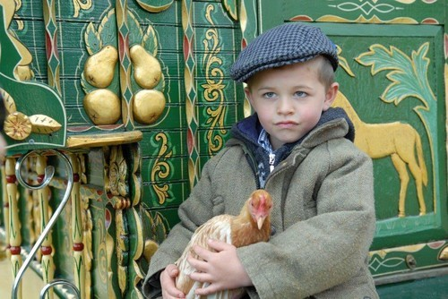 Boy holding Chicken in front of Romany Gypsy wagon wearing blue cap and green jacket