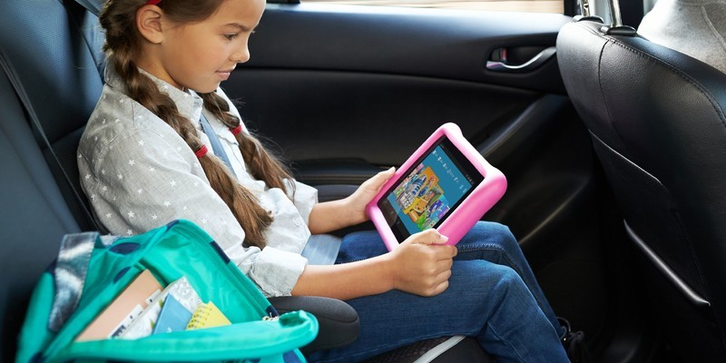 young girl sat in car with iPad