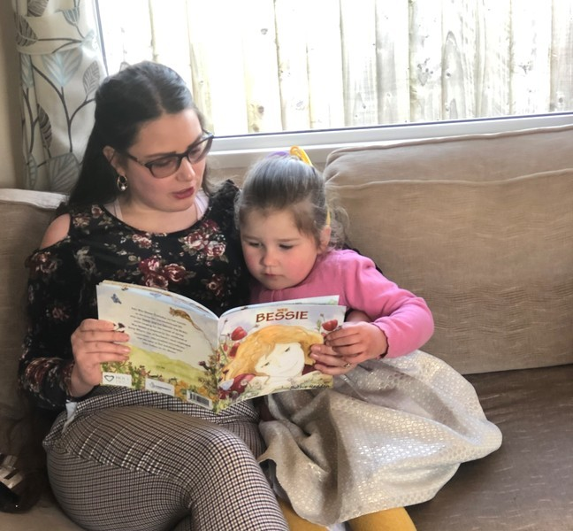 Woman reading book to young girl on sofa