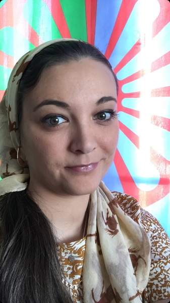 A photo of Nikki Hughes wearing a cream headscarf and gold earings smiling in front of the red and green Romani flag.