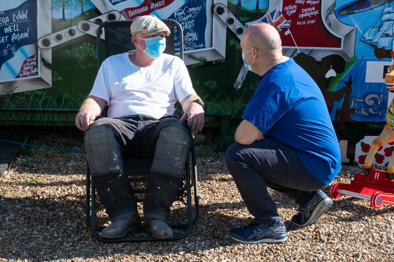 Man on deckchair with covid mask on talking to doctor