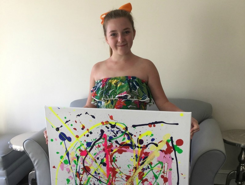 Young girl Samantha Brian with a painting she completed for her Arts Award