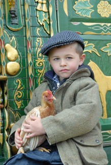 Young boy holding a chicken sat on porch of green Romany wagon with gold paintings on.