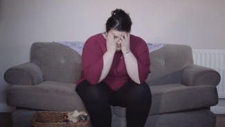 Women sat on sofa with hands over her face looking stressed