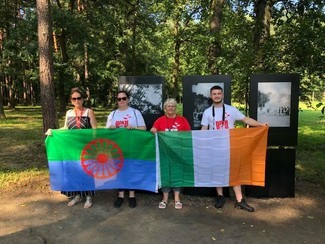 3 women standing with Roma flag and Irish flag