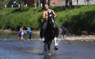 A young Traveller man rides a horse through the River Eden at Appleby Horse Fair – A REAL original Gypsy and Traveller fair established quite a few centuries ago