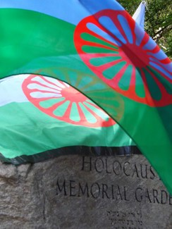 roma flags and the Holocaust memorial stone