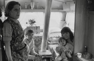 Grandmother with two daughters and granddaughter. Travellers. Inside caravan with stove. 1971. Barnsley. South Yorkshire. © KIERON FARROW.