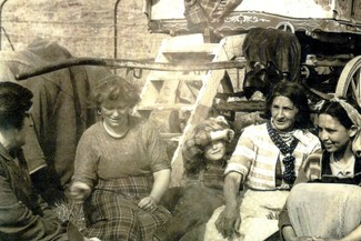 Romany Women sat outside of a wagon around a fire with a kettle on a prop in the middle