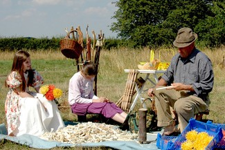 Young girls being showed how to create wooden flowers by a man